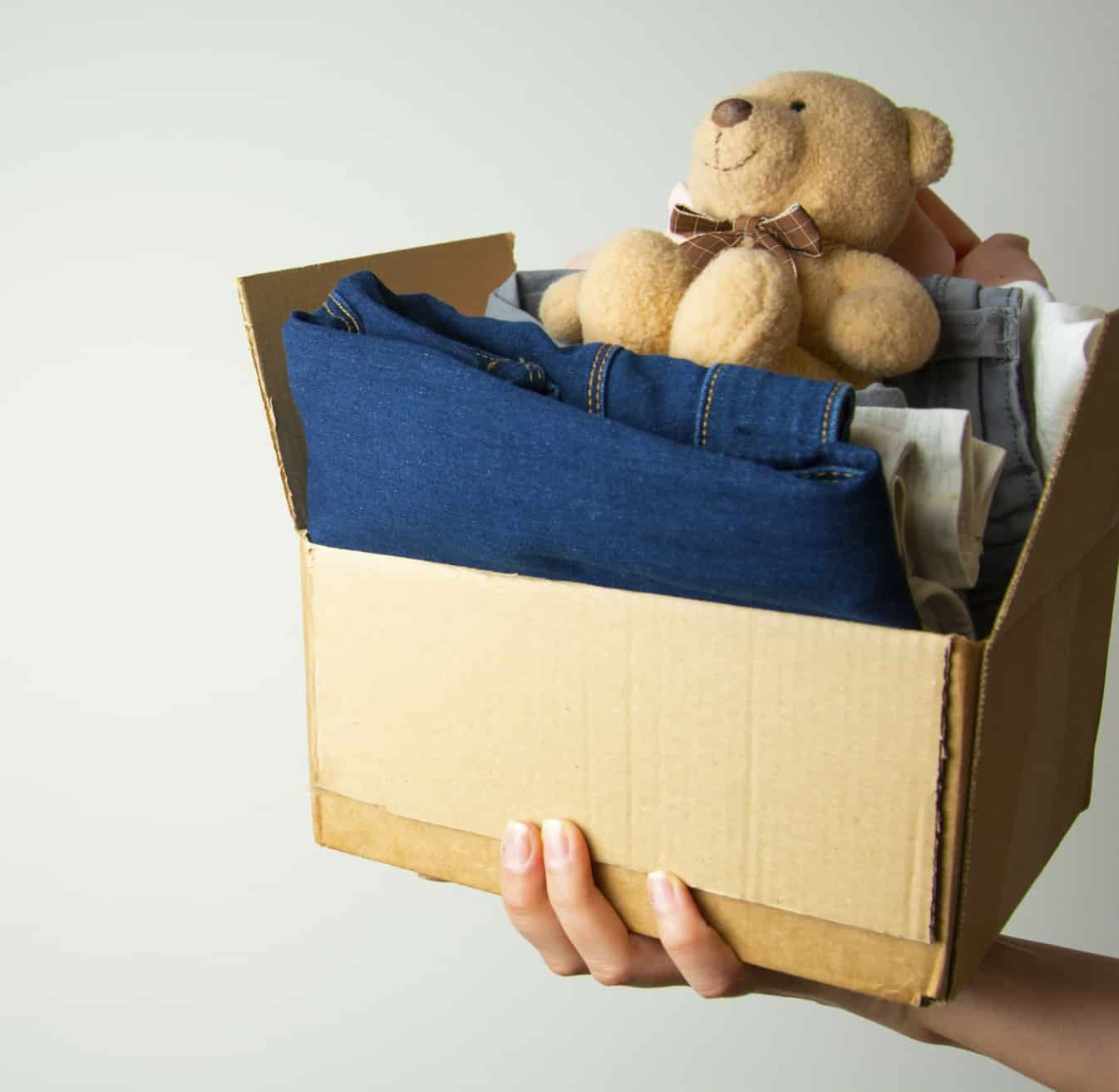 Donation concept. Hands holding donate box with clothes. Copy space.