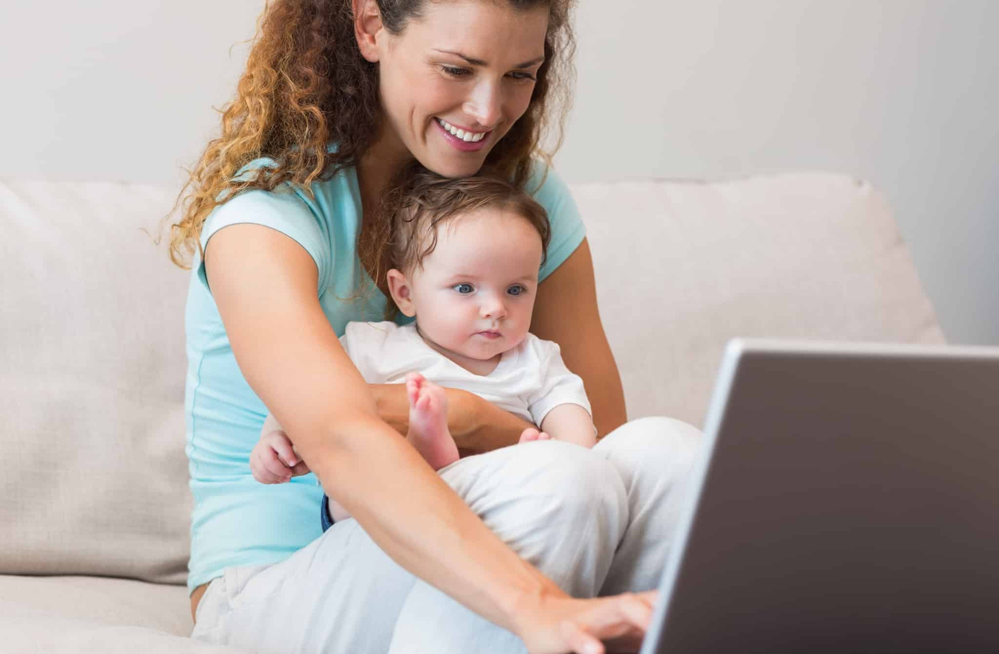 Smiling mother using laptop while holding baby in living room