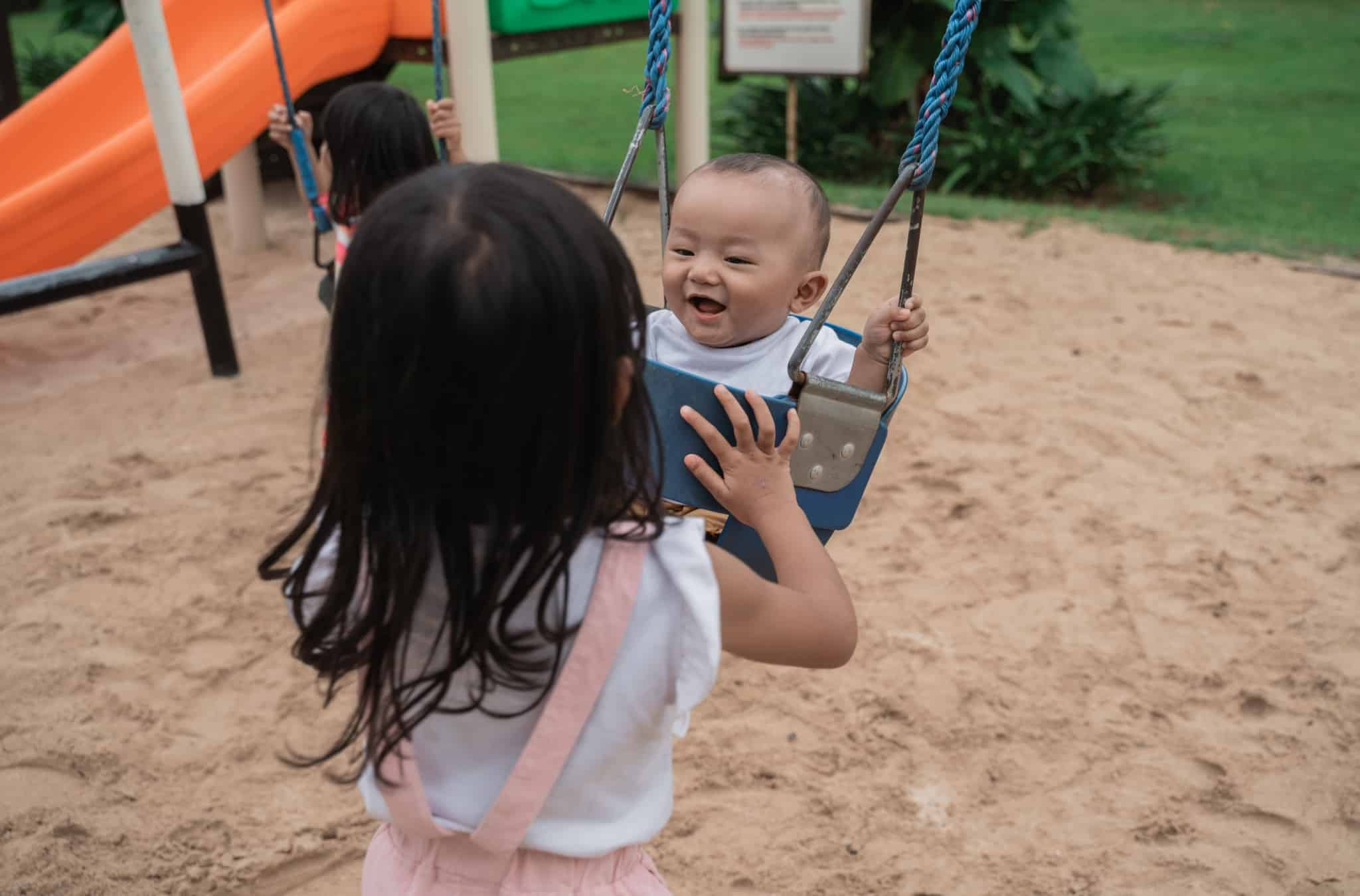 older sibling looking after his baby sister who swings