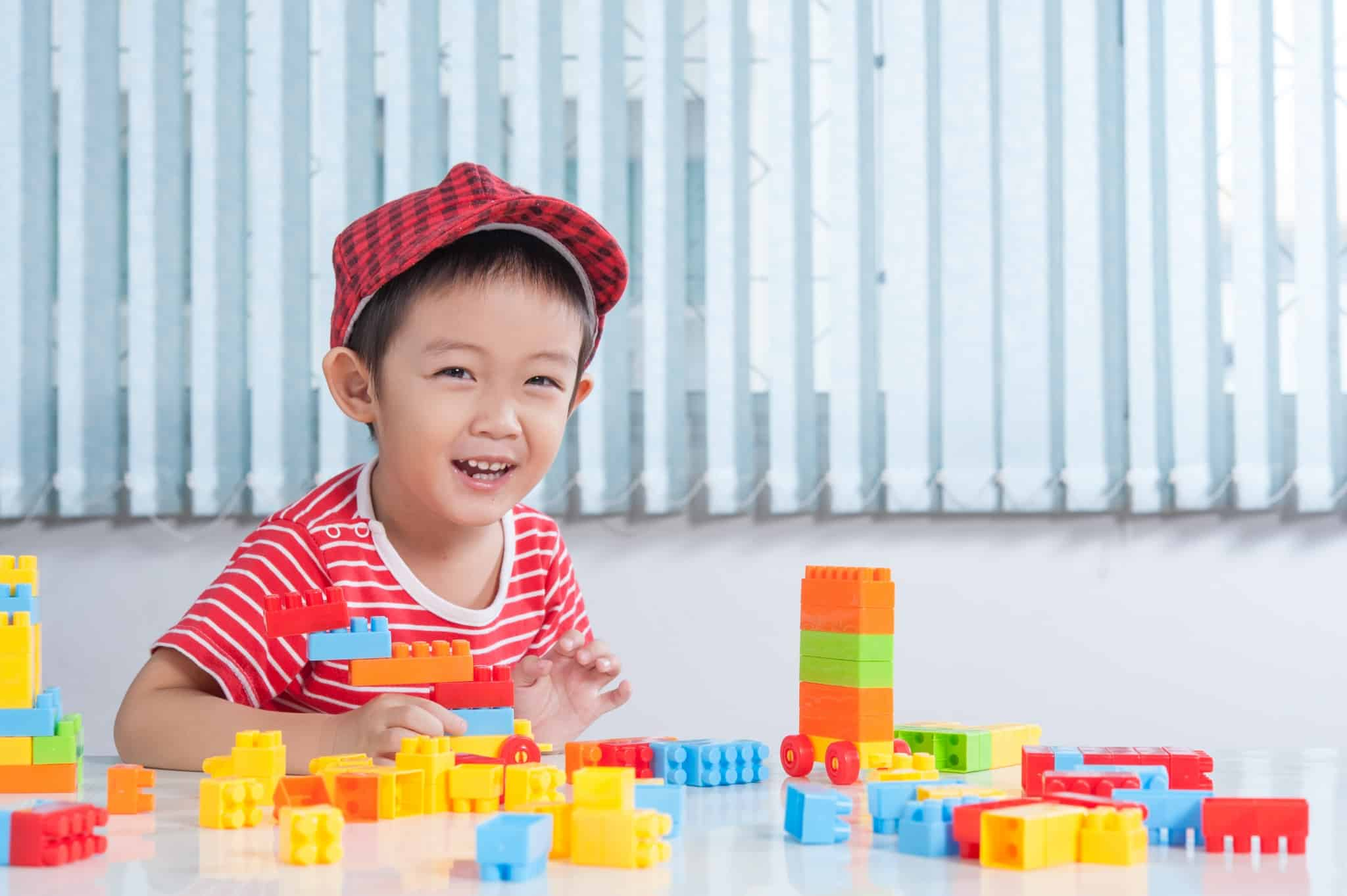 Cute boy playing with colorful plastic bricks at the table in th