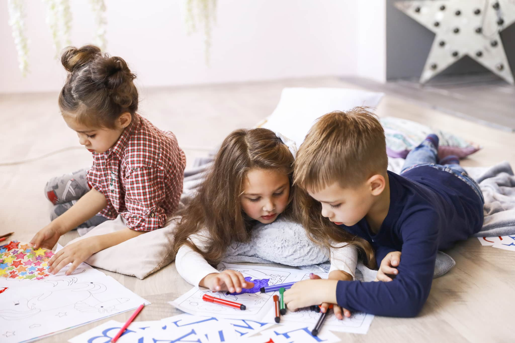 Three focused children are playing on the floor and drawing in c