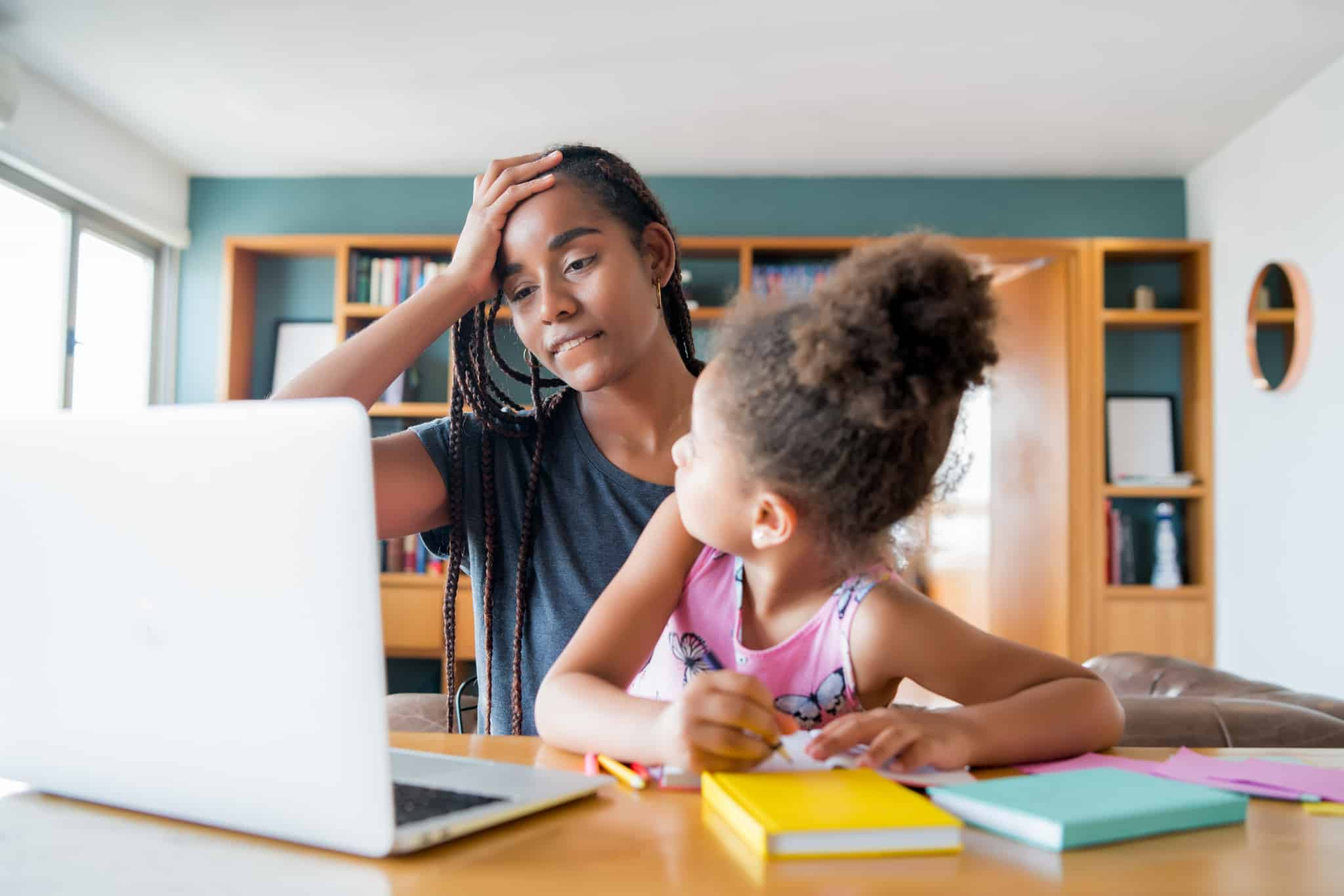 A mother helping her daughter with homeschool.